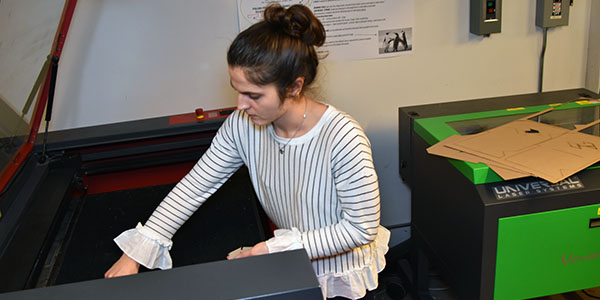 A student uses a laser printer in the fabrication lab