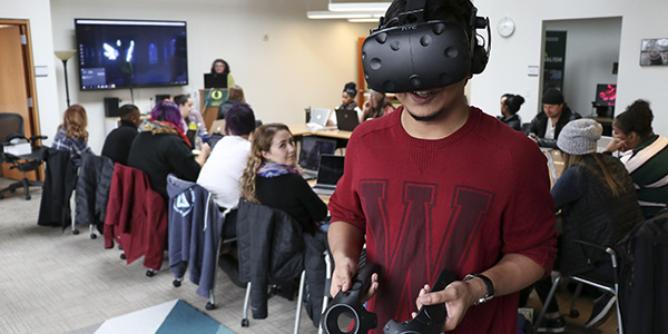 Student wearing a virtual reality headset with a class behind him
